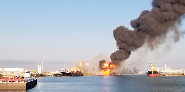 In this photo released by the U.S. Coast Guard, Coast Guard crews respond to a fire dredger in the ship channel of the Port of Corpus Christi August 21 in Corpus Christi, Texas.  Authorities said several people were hospitalized after an explosion in the port of Texas when a dredger hit a natural gas pipeline in the water.  (U.S. Coast Guard via AP)