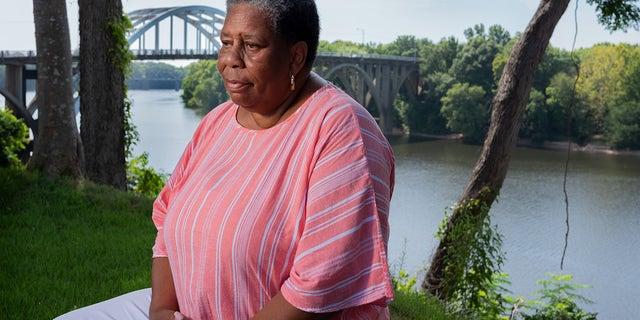 Joanne Bland sitting near the Edmund Pettus Bridge.