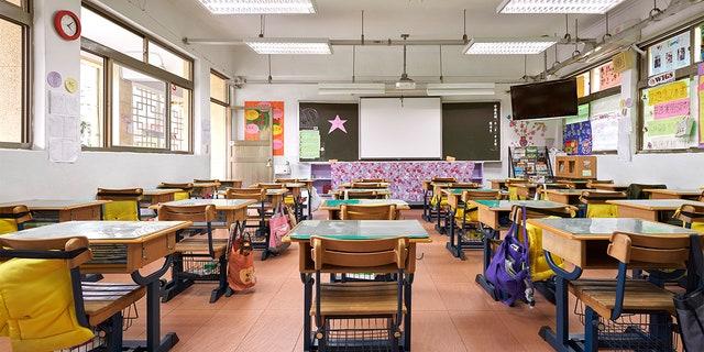 Interior of classroom in elementary school. Row of empty desks are in illuminated room.