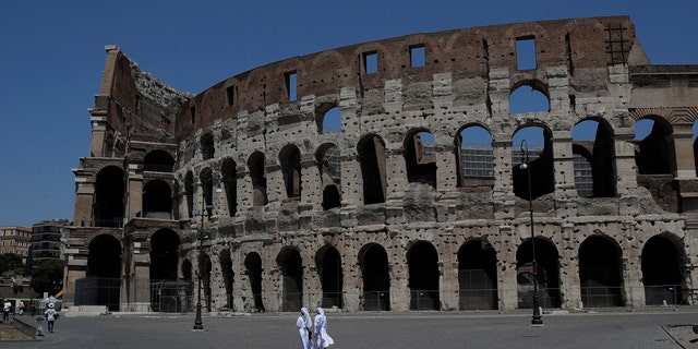 Nuns walk on a hot summer day in front of Rome's Colosseum, Saturday, Aug. 1, 2020.