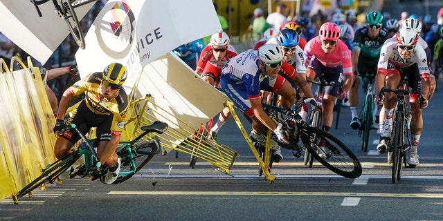 Dutch cyclist Dylan Groenewegen crashes to the ground as a bicycle is flying overhead in a major collision on the final stretch of the opening stage of the Tour de Pologne race in Katowice, Poland, Wednesday, Aug. 5, 2020. (AP Photo/Tomasz Markowski)<br>