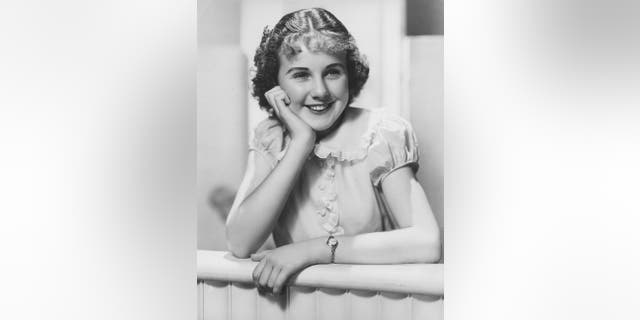 Deanna Durbin, Canadian-born singer and actress, pictured smiling with her chin resting on her right hand, circa 1935. Durbin appeared in a number of musical films in the 1930s and 1940s singing standards as well as operatic arias.