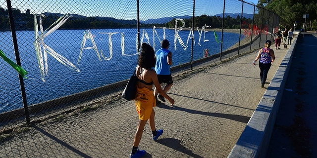 People walk past a chain-link fence surrounding Silver Lake Reservoir in Los Angeles, where an art installation protesting police brutality spells out, in colourful woven fabric, the names of unarmed African Americans who have been killed by police.