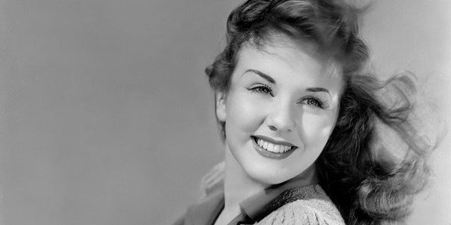 Deanna Durbin (1921-2013) with the wind in the hair and leaning on a tree's branch in a publicity shot from 1941, United States.