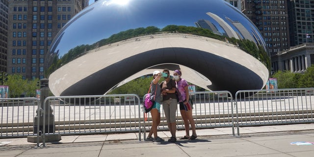 Visitors take pictures in front of the Cloud Gate sculpture in Millennium Park on June 15 in Chicago, Illinois. (Scott Olson/Getty Images)