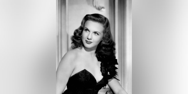 Canadian actress and singer Deanna Durbin (1921-2013) wearing a black sleeveless dress in a publicity shot once used for the cover of the magazine Yank, The Army Weekly, 1944, United States.
