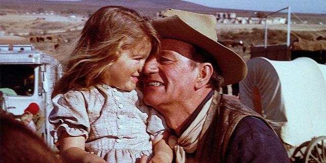 John Wayne hugs his daughter, Aissa, on the set of 'The Alamo.'