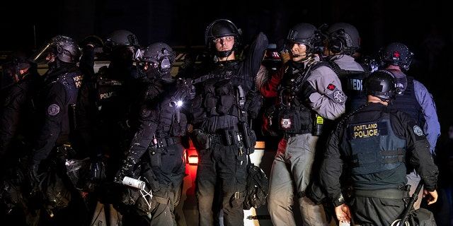 Portland police are seen in riot gear during a standoff with protesters in Portland, Oregon on August 16, 2020. (Photo by Paula Bronstein/Getty Images )