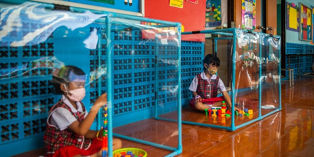 Thai kindergarten students wear face masks as they play in screened-in play areas used for social distancing at the Wat Khlong Toey School in Bangkok. (Getty Images)