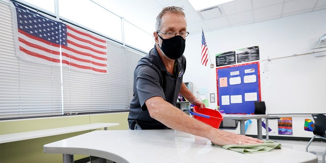 July 29, 2020: Custodian Doug Blackmer cleans a desk in a classroom at the Jesse Franklin Taylor Education Center in Des Moines, Iowa.
