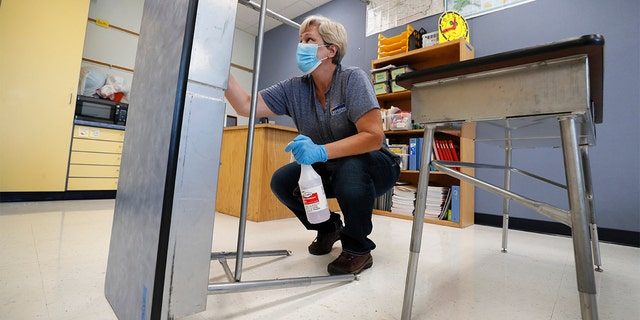 FILE - In this July 8, 2020, file photo, Des Moines Public Schools custodian Cynthia Adams cleans a desk in a classroom at Brubaker Elementary School in Des Moines, Iowa. An aggressive push by Iowa's staunchly pro-Trump governor to reopen schools amid a worsening coronavirus outbreak has descended into chaos, with some districts and teachers rebelling and experts questioning the scientific benchmarks being used by the state to make decisions. (AP Photo/Charlie Neibergall, File)
