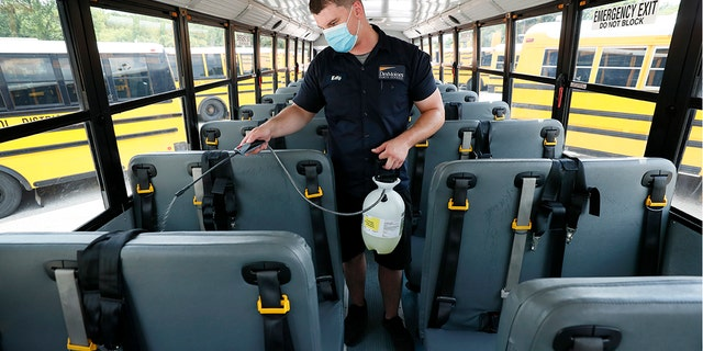 In this July 29, 2020, file photo, Des Moines Public Schools mechanic Kelly Silver cleans the interior of a school bus in Des Moines, Iowa.
