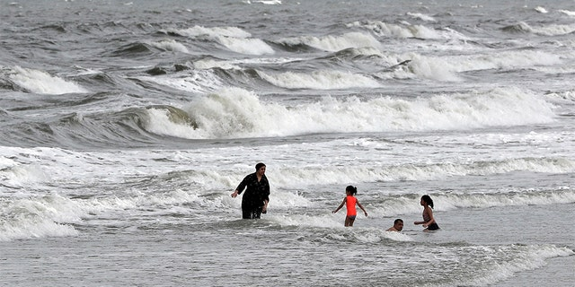 People swim in the ocean as Tropical Storm Isaias approaches in Kure Beach, N.C., Monday, Aug. 3, 2020.