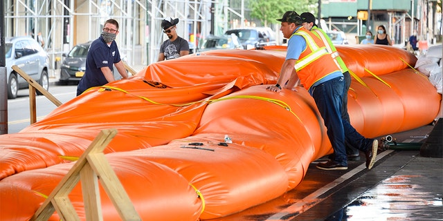 Workers erect temporary flood barriers in the South Street Seaport neighborhood in preparation for potential flooding and a storm surge from Tropical Storm Isaias on August 03, 2020 in New York City. The storm, which is heading up the East Coast packing heavy winds, is expected to dump several inches of rain on the metro area starting late this evening and into tomorrow. The interlocking tubes, called Tiger Dams, are installed in areas that were heavily damaged from flooding during Hurricane Sandy.