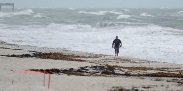 A beach goer walks along the shore as waves churned up by Tropical Storm Isaias crash near Jaycee Beach Park, Sunday, Aug. 2, 2020, in Vero Beach, Fla.