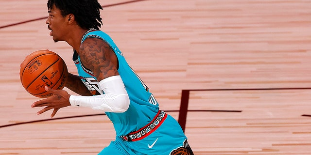 Ja Morant of the Memphis Grizzlies dribbles down court during the first half of an NBA basketball game Sunday, Aug. 9, 2020, in Lake Buena Vista, Fla. (Kevin C. Cox/Pool Photo via AP)