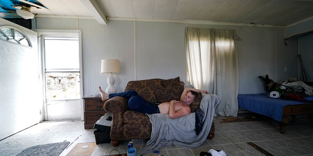 James Townley, who has a heart condition, lies on his couch with no electricity in his partially destroyed mobile home in Lake Charles, La., in the aftermath of Hurricane Laura, Sunday, Aug. 30, 2020.