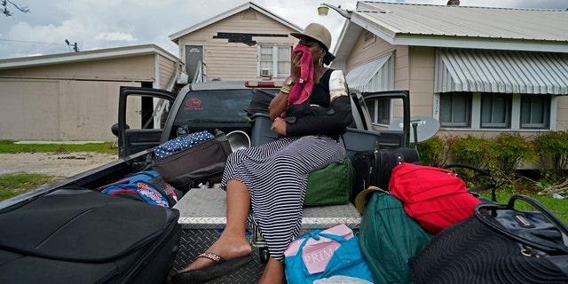 Rakisha Murray cries in relief as she arrives to see her mother's home largely undamaged, after she returned from evacuation with her mother and other family in Lake Charles, La., in the aftermath of Hurricane Laura, Sunday, Aug. 30, 2020.