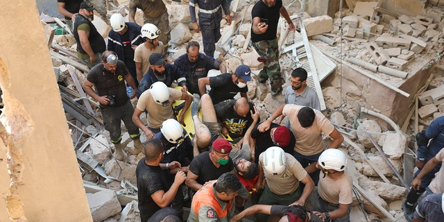 A survivor is taken out of the rubble after a massive explosion in Beirut, Lebanon, Wednesday, Aug. 5, 2020. (AP Photo/Hassan Ammar)