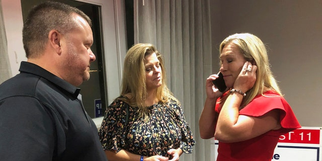 Supporters stand with construction executive Marjorie Taylor Greene, right, as she's on the phone, late Tuesday, Aug. 11, 2020, in Rome, Ga. Greene, criticized for promoting racist videos and adamantly supporting the far-right QAnon conspiracy theory, won the GOP nomination for northwest Georgia's 14th Congressional District. (AP Photo/Mike Stewart)