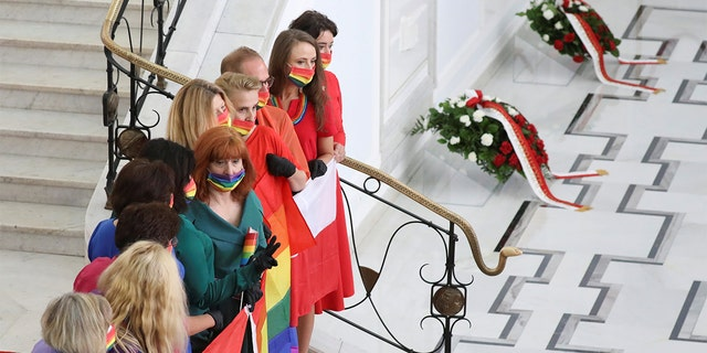 Members of parliament wearing rainbow-themed masks, representing the LGBT symbol, pose for a picture after the swearing-in ceremony of Andrzej Duda as Polish President in Warsaw, Poland August 6, 2020.