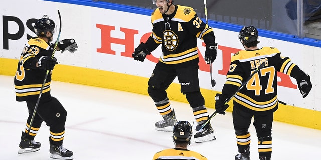 Boston Bruins center Patrice Bergeron (37) reacts with teammates Brad Marchand (63) Torey Krug (47) and Brandon Carlo (25) after scoring the game-winning goal against the Carolina Hurricanes during the second overtime period of an NHL Eastern Conference Stanley Cup playoff game in Toronto on Wednesday, Aug. 12, 2020. (AP)