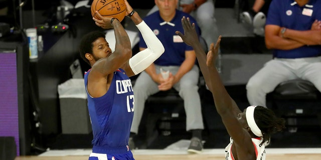 Los Angeles Clippers guard Paul George (13) shoots over Portland Trail Blazers forward Wenyen Gabriel (35) during the first half of an NBA basketball game Saturday, Aug. 8, 2020, in Lake Buena Vista, Fla. (Kim Klement/Pool Photo via AP)
