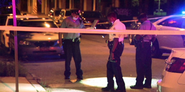 Police work the scene where five people were shot as they were attending a large block party in Philadelphia.
