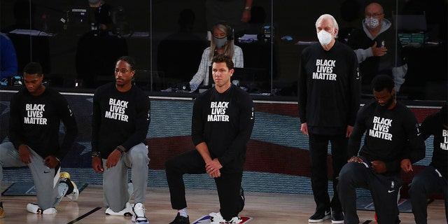 San Antonio Spurs head coach Gregg Popovich, fourth from left, stands while wearing a mask while Sacramento Kings head coach Luke Walton, center, kneels with players before an NBA basketball game Friday, July 31, 2020, in Lake Buena Vista, Fla. (Kim Klement/Pool Photo via AP)