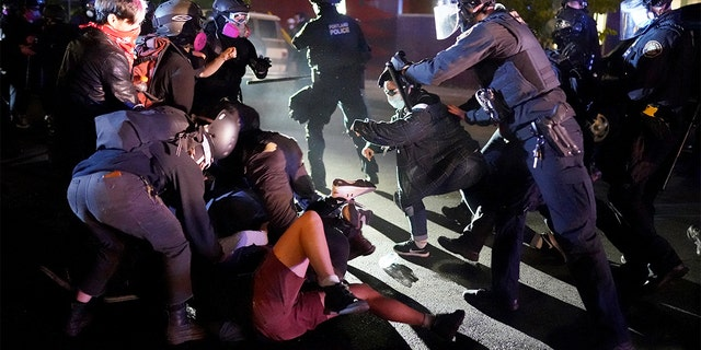PORTLAND, OR - AUGUST 22: Protesters and Portland police clash while dispersing a crowd gathered in front of the Portland Police Bureau North Precinct early in the morning on August 22, 2020 in Portland, Oregon. Friday marked the 86th night of protests in Portland following the death of George Floyd. (Photo by Nathan Howard/Getty Images)