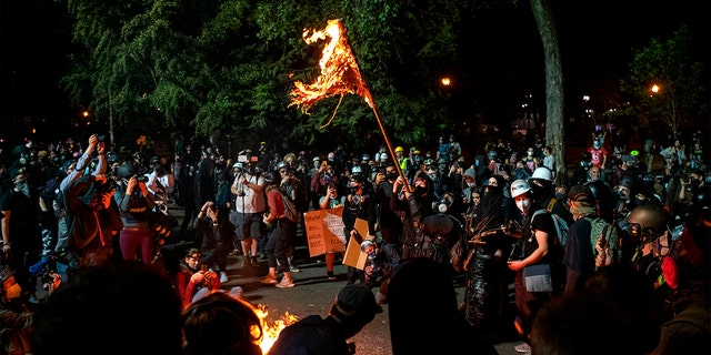 A demonstrator burns an American flag outside the Mark O. Hatfield United States Courthouse late Friday night during the protest on July 31, 2020 in Portland, Oregon. (Photo by ALISHA JUCEVIC/AFP via Getty Images)