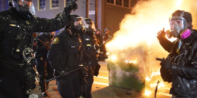 PORTLAND, OR - AUGUST 21: Portland police officers push protesters past a dumpster fire during a dispersal from in front of the Immigration and Customs Enforcement (ICE) detention facility in the early morning on August 21, 2020 in Portland, Oregon. For the second night in a row city police and federal officers clashed with protesters in the South Waterfront. (Photo by Nathan Howard/Getty Images)