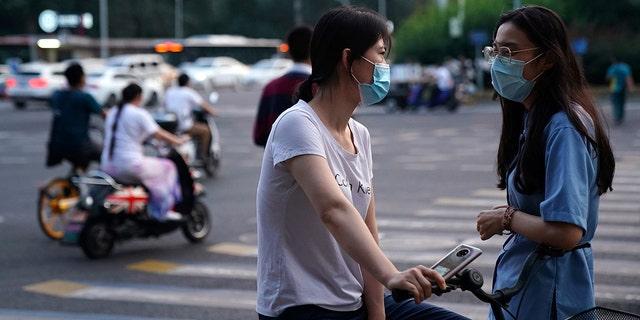 Women wearing face masks following the coronavirus disease (COVID-19) outbreak chat on a street in Beijing, China August 11, 2020. (REUTERS/Tingshu Wang)