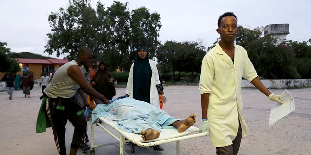 Paramedics and civilians carry an injured person on a stretcher at Madina hospital after a blast at the Elite Hotel in Lido beach in Mogadishu, Somalia August 16, 2020. (Reuters/Feisal Omar)