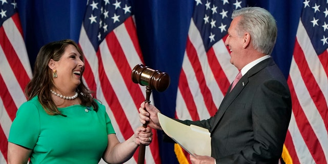 Republican National Committee Chairwoman Ronna McDaniel hands the gavel to House Minority Leader Kevin McCarthy of California before he speaks during the first day of the Republican National Convention on Monday, Aug. 24, 2020, in Charlotte, N.C. (AP Photo/Chris Carlson)