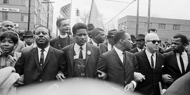 In this March 17, 1965, file photo, Dr. Martin Luther King Jr., fourth from left, foreground, locks arms with his aides as he leads a march of several thousands to the courthouse in Montgomery, Ala. From left are: an unidentified woman, Rev. Ralph Abernathy, James Foreman, King, Jesse Douglas Sr., and John Lewis.