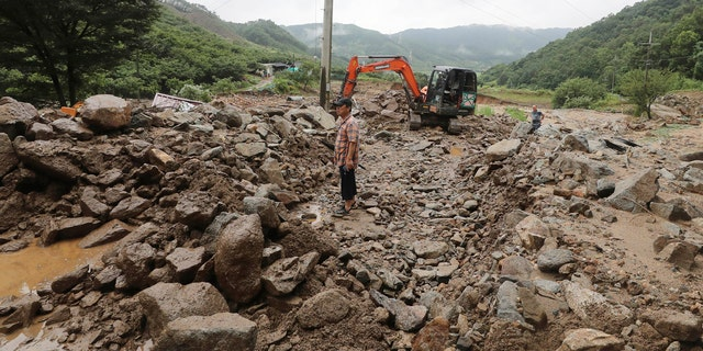 A man stands on road covered with mud and rocks after heavy rains in Chungju, South Korea, Sunday, Aug. 2, 2020.