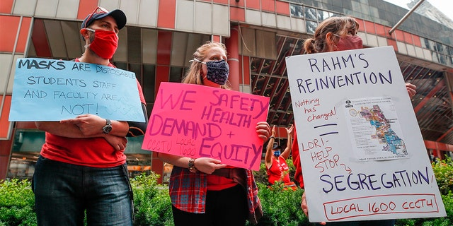 Protesters hold signs during the Occupy City Hall Protest and Car Caravan hosted by Chicago Teachers Union in Chicago, Illinois, on August 3, 2020. - Teachers and activists hold car caravan all over the country on August 3, 2020 to demand adequate classroom safety measures as schools debate reopening.