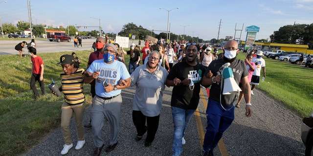 Marja Broussard, center, president of the Lafayette chapter of the NAACP, walking down Evangline Thruway with others demanding justice for Trayford Pellerin on Saturday in Lafayette, La.