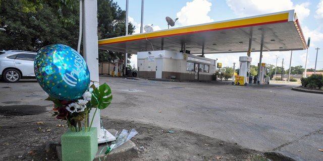 A makeshift memorial on the ground at a Shell station Saturday in Lafayette, La., for 31-year-old Trayford Pellerin.