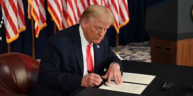 US President Donald Trump signs executive orders extending coronavirus economic relief, during a news conference in Bedminster, New Jersey, on Aug. 8.