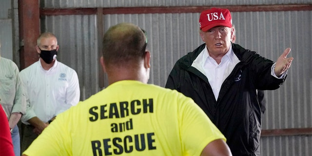 President Donald Trump speaks with first responders as he tours a warehouse being used as a distribution point for relief aid after Hurricane Laura hit the area, Aug. 29, in Lake Charles, La. (AP Photo/Alex Brandon)