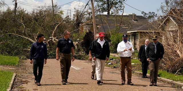 President Trump talks with Louisiana Gov. John Bel Edwards, in white shirt, as he tours damage from Hurricane Laura, Saturday, Aug. 29, 2020, in Lake Charles, La.