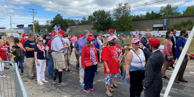 Supporters of President Trump wait in line for a temperature check before as they arrive for the president's speech in Manchester, New Hampshire, on Aug. 28.