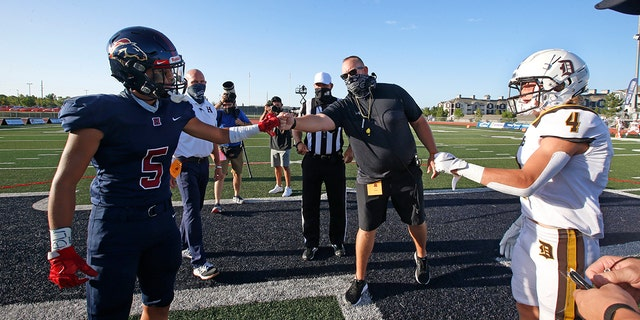 Davis High head coach Mitch Arquette, center, fist bumps Herriman High's Brock Hollingsworth (5) during the coin toss before the start of a high school football game on Thursday, Aug. 13, 2020, in Herriman, Utah. Utah is among the states going forward with high school football this fall. (AP Photo/Rick Bowmer)