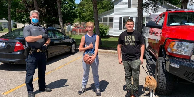 "The Wayland Police Department made Austin Nichols, 13, and Logan Mishoe, 14, holding dog, honorary ""Citizens of the Day"" after finding a cash-filled wallet in a park and turning it in to an officer."