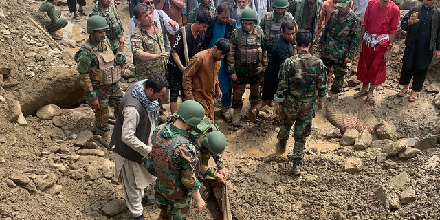 Soldiers and locals search for victims in a mudslide following heavy flooding in the Parwan province, north of Kabul, Afghanistan, Wednesday, Aug. 26, 2020.