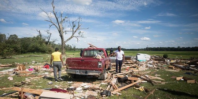 Relatives of a woman who was injured when a suspected tornado ripped through the area southeast of Windsor, N.C. sort through the rubble on Tuesday, Aug. 4, 2020.