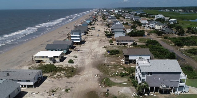 Oak Island sustained wind and flood damage caused by Hurricane Isaias leaving the streets strewn with debris and covered with more than a foot of sand in areas close to the beach Tuesday, August 4, 2020, in North Carolina.