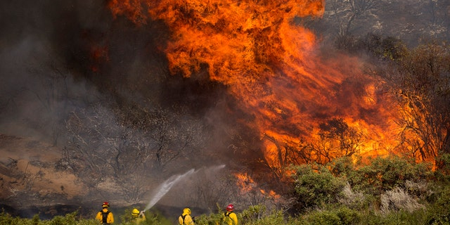 Firefighters work against the Apple Fire near Banning, Calif., Sunday, Aug. 2, 2020.
